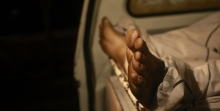 The feet of a man, who was killed in a shootout with police, are seen from an ambulance outside a Karachi hospital