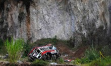 A view shows an autobus at its crash site after going off a cliff in San Martin Jilotepeque